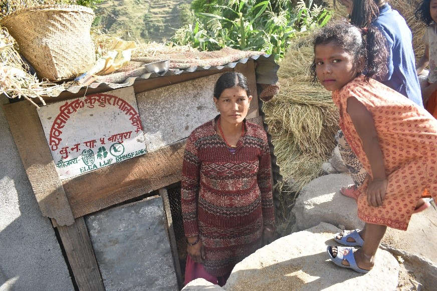 Ms. Suntali Kami in front of her Poultry Farm
